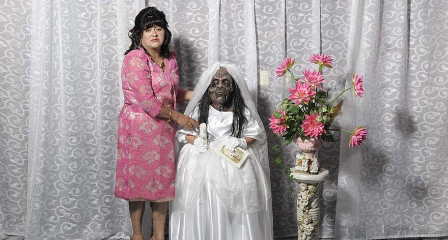 Foto de una señora sosteniendo a una niña momificada en vestido blanco a un costado de un ramo de flores tomada por el fotógrafo Diego Moreno