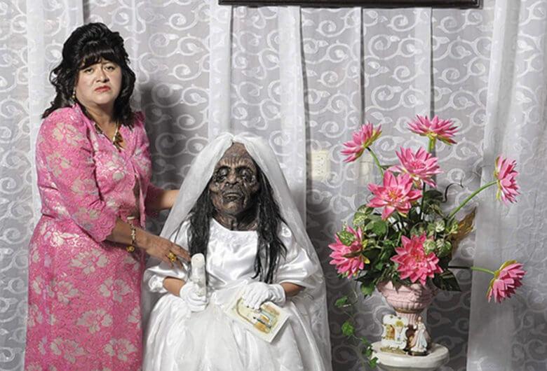 Foto de una señora sosteniendo a una niña momificada en vestido blanco a un costado de un ramo de flores Fotografía de Diego Moreno